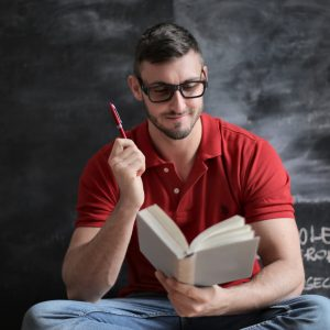 man-in-red-polo-shirt-and-blue-denim-jeans-holding-red-pen-3779488